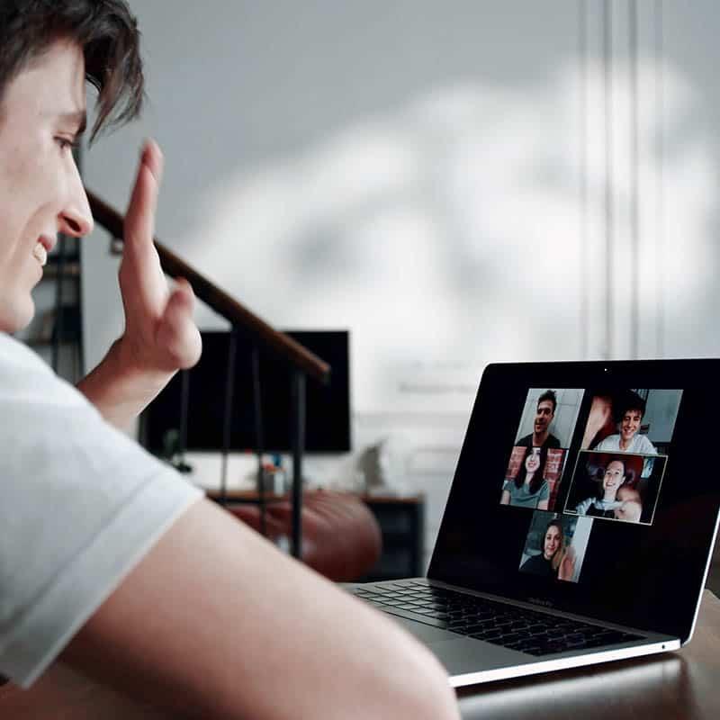 Mann winkt im Zoom Meeting in die Kamera