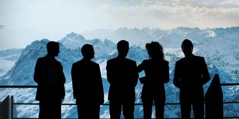 Fünf Menschen vor einem Bergpanorama während einer Konferenz