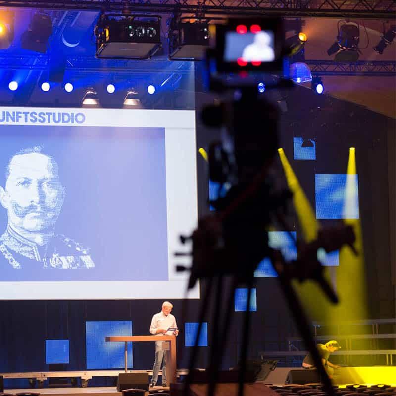 Ein Mann steht auf einer großen Bühne