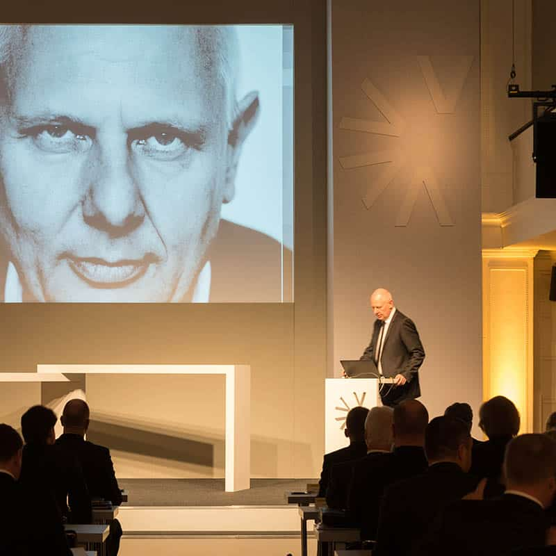 Ein Mann präsentiert auf einer Konferenz auf dem Podium